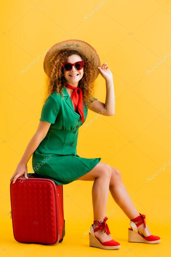 Full length of cheerful woman in straw hat, sunglasses and dress sitting on luggage on yellow stock vector
