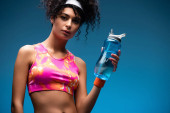 curly woman in sportswear holding sports bottle with water on blue