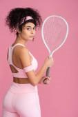 mladá žena ve sportovním oblečení držení tenisové rakety izolované na růžové