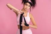 lockige junge Frau in Sportbekleidung, die Hand mit schwarzer Fessel auf rosa isoliert