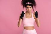 lockige junge Frau in Sportbekleidung mit Fesseln an den Händen isoliert auf rosa