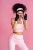 starke junge Frau in Sportbekleidung mit Fesseln an den Händen isoliert auf rosa
