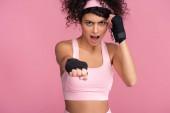 lockige junge Frau in Sportbekleidung mit Fesseln an den Händen schreit, während sie isoliert auf rosa trainiert