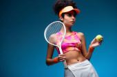 sportovní a kudrnatá žena držící tenisovou raketu a míček na modré
