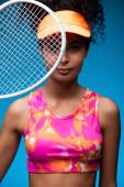 sportovní mladá žena v čepici při pohledu na kameru přes tenisovou raketu na modré