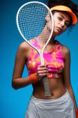 sportovní mladá žena držící tenisovou raketu při pohledu na kameru na modré