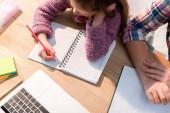 Top kilátás lánya írás notebook közelében anya íróasztal írószer és laptop