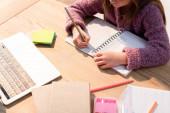 Vágott kilátás lány írás notebook közelében ragadós jegyzetek, könyvek és laptop az asztalon