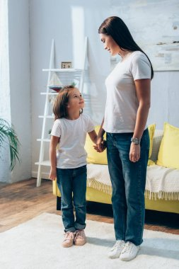 Full length of smiling mother and daughter looking at each other while holding hands at home on blurred background stock vector