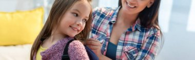 Smiling daughter looking away while mother putting on backpack on blurred background, banner