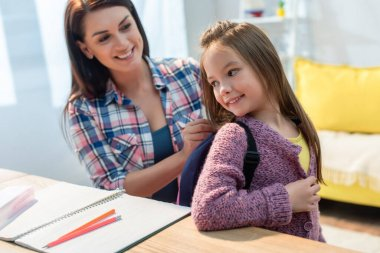 Happy mother putting backpack on daughter near desk at home on blurred background