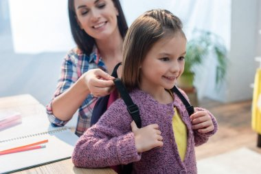 Smiling mother putting backpack on daughter at home on blurred background