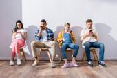 Többnemzetiségű emberek okostelefonokat használnak székeken várakozás közben a hallban