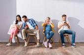 Multikulturní lidé a těhotné ženy pomocí chytrých telefonů a čtení knihy na židlích ve frontě