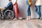Ausgeschnittene Ansicht eines behinderten Mannes mit medizinischer Maske, der im Rollstuhl neben Menschen in der Halle sitzt