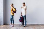 Diák ellenőrzés idő karóra közelében nő hátizsák a hallban