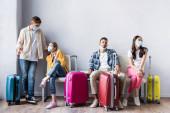 A repülőtéren bőröndök közelében várakozó multikulturális emberek orvosi maszkban
