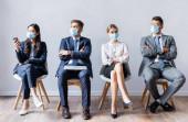 Multikulturelle Geschäftsleute in medizinischen Masken mit Geräten warten auf Vorstellungsgespräch in der Halle