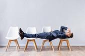 Obchodník v obleku ležící na židlích při čekání na pracovní pohovor