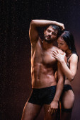 sensual woman in black lace lingerie kissing shoulder of sexy muscular man on dark background under falling rain