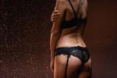 oříznutý pohled na ženu v černé krajky spodní prádlo a suspender pás pod padající kapky deště na tmavém pozadí