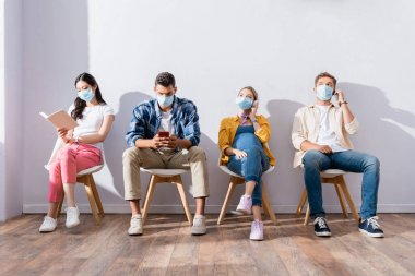 Multicultural people in medical masks using cellphones, headphones and book in queue