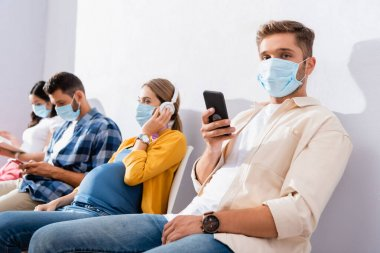 Man in medical mask holding smartphone near pregnant woman in queue