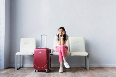 Tired asian woman looking away near suitcase while waiting in airport stock vector