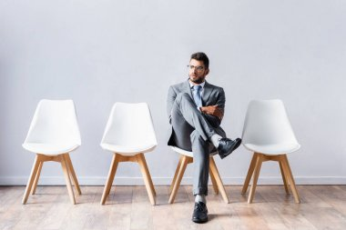 Young businessman sitting with crossed legs on chair in office stock vector