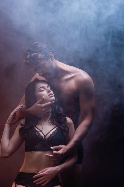 sexy shirtless man hugging neck of seductive woman in black lace lingerie on dark background with smoke