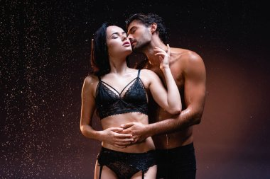 Shirtless man embracing and kissing sexy woman in black underwear under falling rain on dark background stock vector