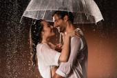 boční pohled na šťastný pár objímání při stání s deštníkem pod deštěm na tmavém pozadí