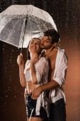 férfi kéz a kézben zsebében boldog nő áll eső alatt esernyő sötét háttér