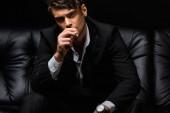 magabiztos férfi öltönyben dohányzik cigaretta és néz kamera elszigetelt fekete
