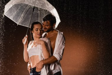 smiling man holding hands in pockets of sexy woman standing under rain with transparent umbrella on dark background