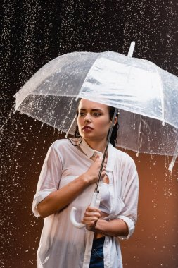young woman in wet white shirt standing under rain with transparent umbrella on dark background