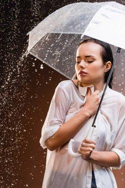 woman in wet shirt standing with umbrella under rain on dark background