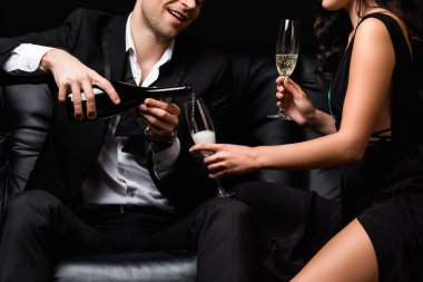 Cropped view of happy man in suit holding bottle while pouring champagne in glass near sexy woman in dress stock vector