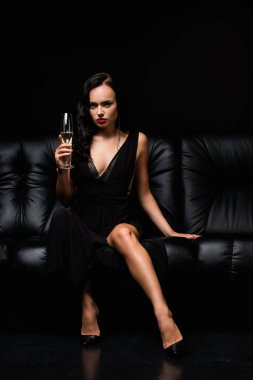 Brunette woman in dress sitting on sofa and holding glass of champagne on black stock vector