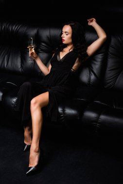 Seductive woman in dress sitting on sofa and holding glass with champagne on black stock vector