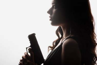 Side view of brunette young woman holding gun isolated on white stock vector