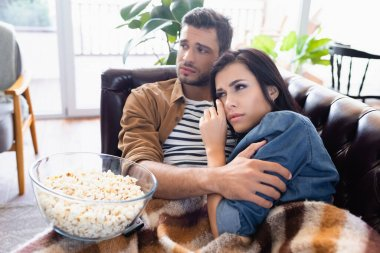 Worried couple watching movie near bowl of popcorn at home stock vector