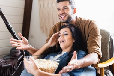 Excited man pointing with hands while watching tv with girlfriend holding bowl of popcorn stock vector