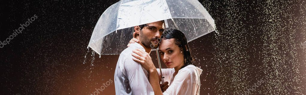Young couple in wet shirts embracing and looking at camera while standing under rain with umbrella on dark background, banner stock vector