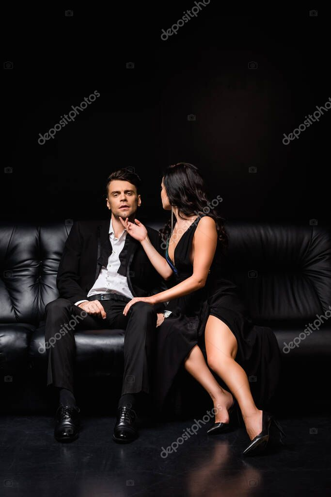 Full length of elegant woman in dress sitting on couch with man in suit on black stock vector