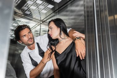 Passionate man seducing sexy woman in black satin dress in elevator, blurred foreground stock vector