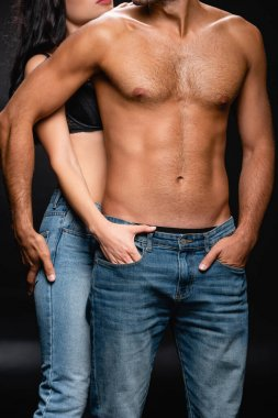 cropped view of seductive woman holding hand in pocket of jeans of muscular man on black