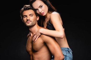Shirtless muscular man piggybacking seductive woman looking at camera isolated on black stock vector