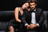 sexy žena v saténových šatech ležící na rameni elegantního muže sedí na koženém gauči izolované na černé