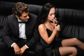 seductive woman in satin dress and stockings lighting cigarette near elegant man isolated on black